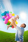 Father throws daughter. Family playing together in park with balloons. Father tosses a baby against