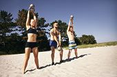 stock photo of snatch  - Group of athletes swinging a kettle bell over their head on beach - JPG