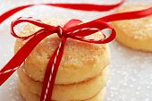 Freshly baked sugar cookies tied with festive bakers twine and red satin ribbon.  Decorating sugar c
