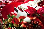 Red electric guitar with white blank card in front for your message. Concept image for holiday music