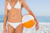 Sexy female body in white bikini with beach ball on the beach