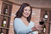 Mature Woman Looking at Wineglass, Winetasting