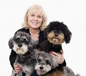 Portrait of woman embracing her dogs, studio shot