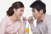 Young couple sharing a glass of orange juice, studio shot