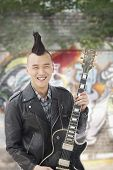 Young man with punk Mohawk holding guitar