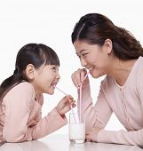 Mother and daughter sharing a glass of milk, studio shot