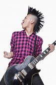 Young man with punk Mohawk playing guitar