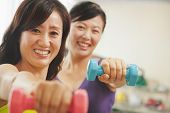 Two mature women lifting weights in the gym and looking at the camera