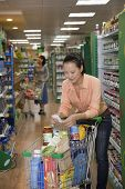 Woman looking at shopping list in supermarket, Beijing
