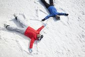 Couple Lying On Snow Making Snow Angel