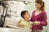 stock photo of medium-  length hair  - Mother and Son Brushing Teeth Together - JPG