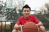 Young man sitting with a basketball on the basketball court, portrait