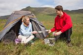 Cheerful couple cooking outdoors on camping trip in the countryside