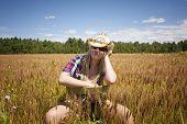 Cowgirl Sitting In Wheat Field