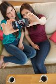 Two friends on the couch taking a selfie with smartphone at home in the living room