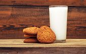 glass of milk and oat cookies on wooden background