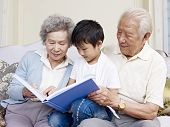 image of grandparent child  - grandparents and grandson reading a book together - JPG