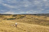 a lonely male biking over rolling prairie illuminated by sunrise at Soapstone Prairie Natural Area i