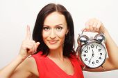 Young happy brunette  woman with alarmclock