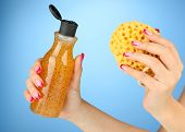 Female hand with wisp and bottle of shower gel, on color background