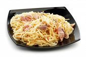 Spaghetti carbonara with fried bacon in black plate on white background