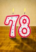 Burning birthday candles number 78 on a wooden background