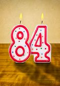 Burning birthday candles number 84 on a wooden background