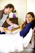 Happy Man Bringing Breakfast In Bed To Girlfriend