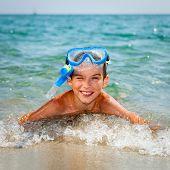 Happy boy wearing snorkeling gear lying in the sea