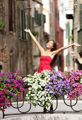 Woman happy in romantic Venice, Italy Girl standing in summer dress on bridge with flowers smiling j