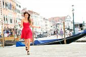 Happy summer girl running in dress in Venice, Italy. Woman smiling laughing joyful having fun by water in Venice. Beautiful multiracial Asian Caucasian young woman in full body length.