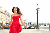 Woman happy running in summer dress, Venice, Italy. Girl smiling laughing joyful having fun by water