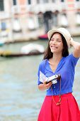 Travel woman tourist traveling in Venice, Italy holding camera and map. Asian girl on vacation smili