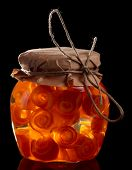 Glass jar with citrus zest preserves isolated on black background