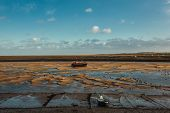 Fishing Boat Anchored At Low Tide