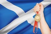 Medal In Hand With Flag On Background - Scotland