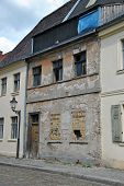 Fassade of an old, damaged House with broken Windows