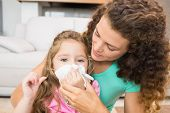 Mother helping her daughter blow her nose at home in living room