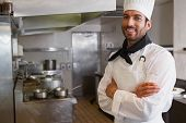 Happy head chef smiling at camera with arms crossed in a commercial kitchen