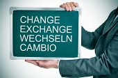 man wearing a suit holding a chalkboard with the words change, exchange, wechseln, cambio written in it