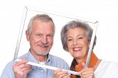 Senior couple with picture frame in front of white background