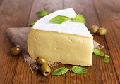 Tasty Camembert cheese with basil and olives, on wooden table