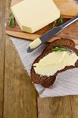 Slice of rye bread with butter on wooden cutting board