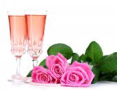 Composition with pink sparkle wine in glasses and pink roses isolated on white