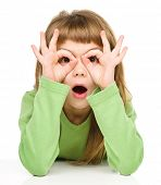 stock photo of unbelievable  - Astonished little girl is showing glasses gesture - JPG