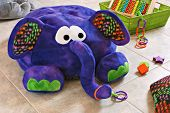 Colorful stuffed elephant with pillow and basket of toys on tile in kids playroom.  (Elephant is a h