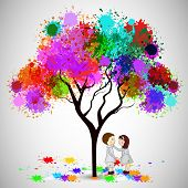 Indian festival Happy Holi celebrations with cute couple under the tree playing with colours on grey background.