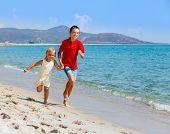 Happy children running along a beach