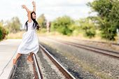 Young girl in a cool white summer frock leaping off a rural deserted train station platform with her arms raised in the air