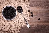 A bowl of fresh blackberries with spoon, over antique lace tablecloth and old wood background. Space for your text.